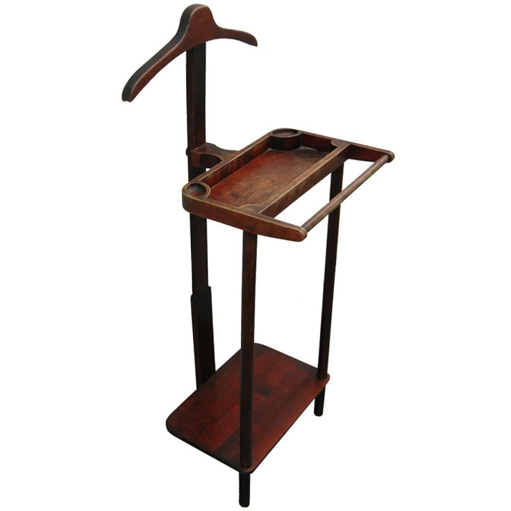 1890 Valet Stand Culture: American Medium: mahogany A vintage wooden valet stand stained in mahogany with a segmented tray with a pants bar at front and a shoe shelf below surmounted by a hanger hook.
