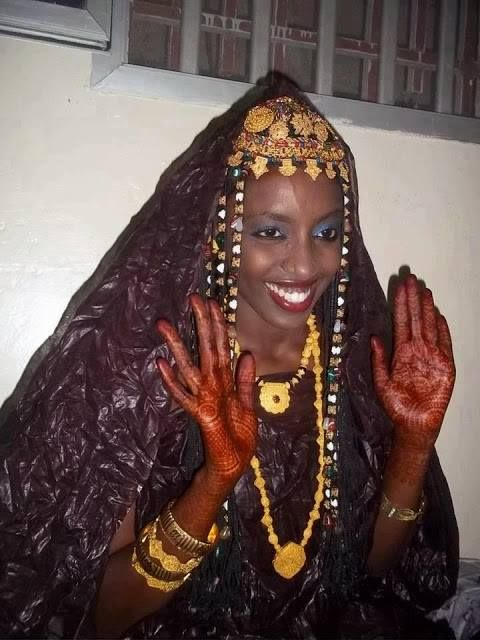 Ethnic Moor (Mauri) bride from Mauritania in West Africa in her traditional attire with her henna palm showing she just got married.