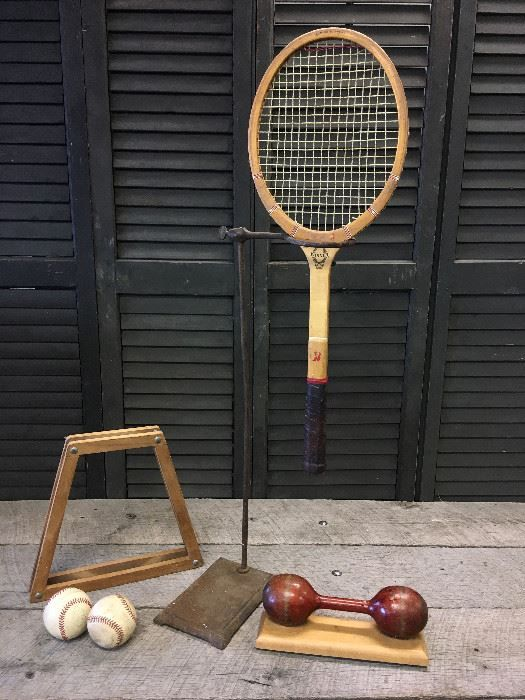 Found on EstateSales.NET: Lot of industrial looking, vintage sports items including 2 baseballs, a vintage tennis racket with cover, on set of vintage wooden dumbbells mounted to a wooden board for display with a cool antique industrial stand you can do almost anything with!