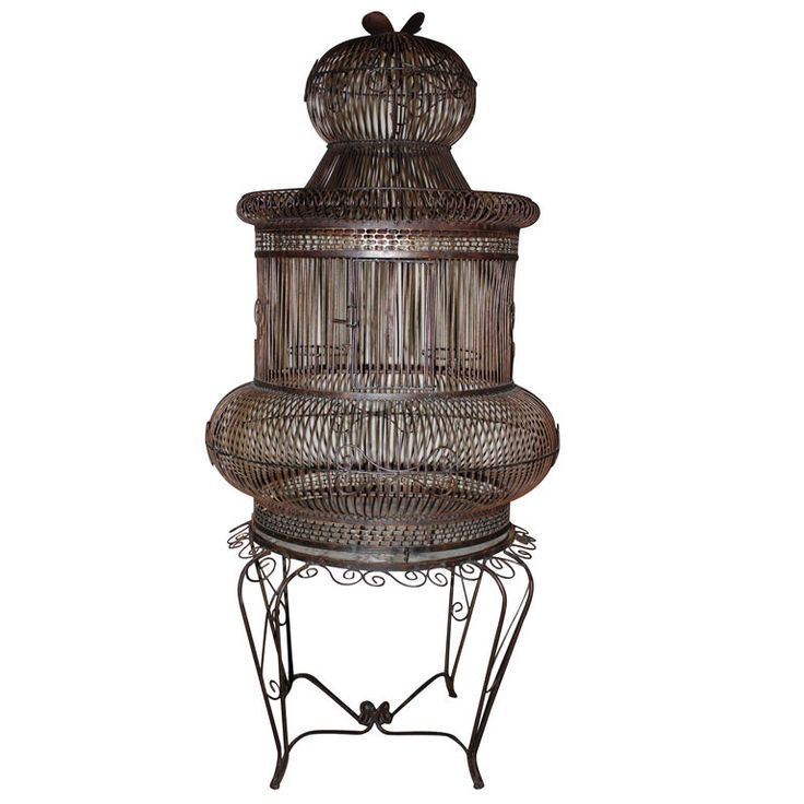 1940's Parrot Cage On Stand In Patinated Steel  USA  1940's  A decorative birdcage in patinated steel, circa 1940, with a separate circular base. The top of the cage has a hook to hang it with and the base can be used as a table by inserting a glass or stone top.