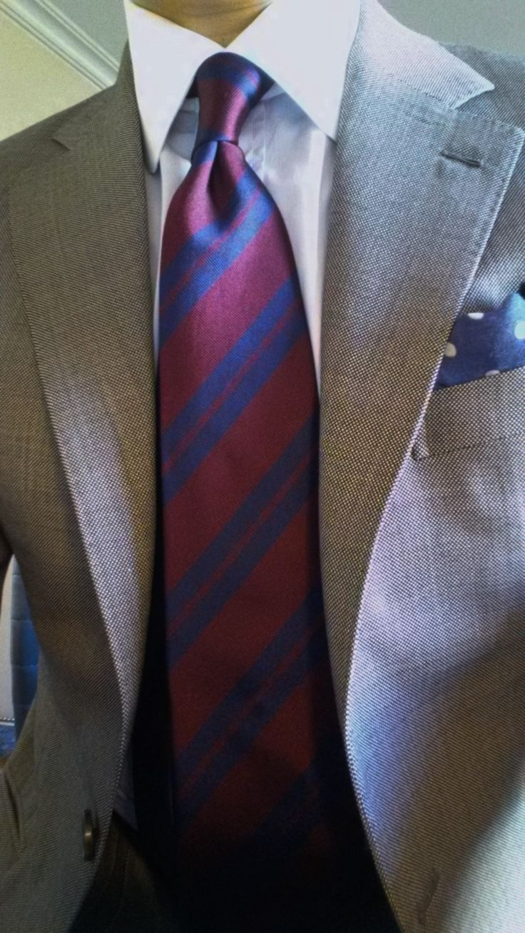 Light grey jacket, white shirt, red tie with navy stripes
