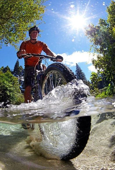 Half underwater view of a mountain biker crossing a stream. New Zealand. - Photo by Chris McLennan