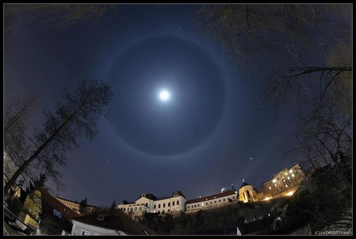 Moon Halo over Veszprem Castle -By: Tamas Ladany. The 22-degree moon halo is photographed in this wide-angle view of the historic Veszprem Castle in Hungary. Large atmospheric halo around the Moon or the sun occurs when high thin clouds containing millions of tiny ice crystals cover much of the sky. Each ice crystal acts like a miniature lens. Because most of the crystals have a similar elongated hexagonal shape, light entering one crystal face and exiting through the opposing face refracts…