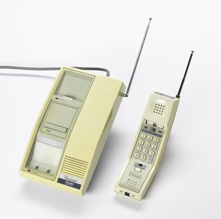 Base unit for 'Freeway'cordless telephone, grey and cream in color, base, battery charger, aerial and electrical cords, by British Telecom, Taiwan, c.1984.