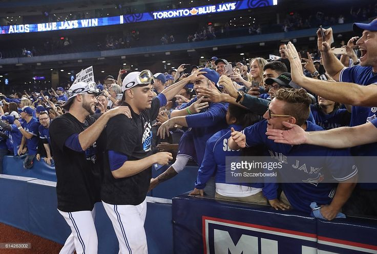 Roberto Osuna #54 of the Toronto Blue Jays and Ryan Tepera #52 celebrate with fans after winning the game and series in the tenth inning during MLB game action against the Texas Rangers in game three of the American League Division Series at Rogers Centre on October 9, 2016 in Toronto, Canada.