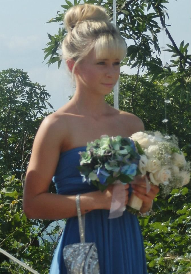 Holly holding brides bouquet at ceremony