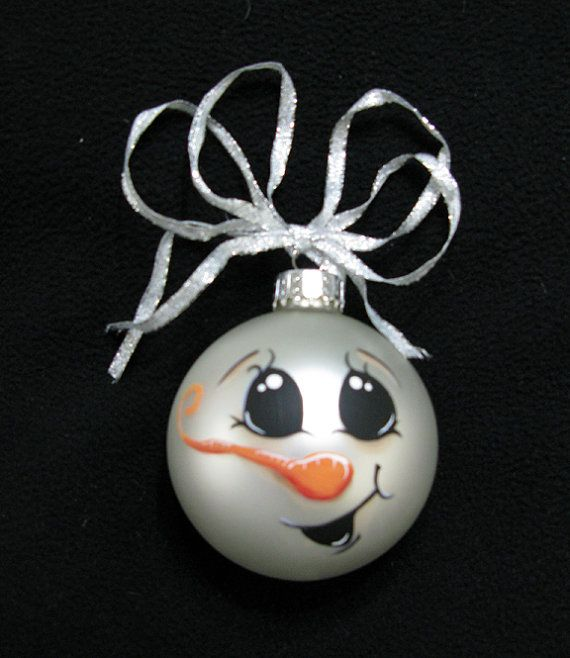 Hes a bright eyed, smiley, little carrot nosed snowman ornament. Decorated with a silver ribbon.    This is a 3 inch glass ball ornament.