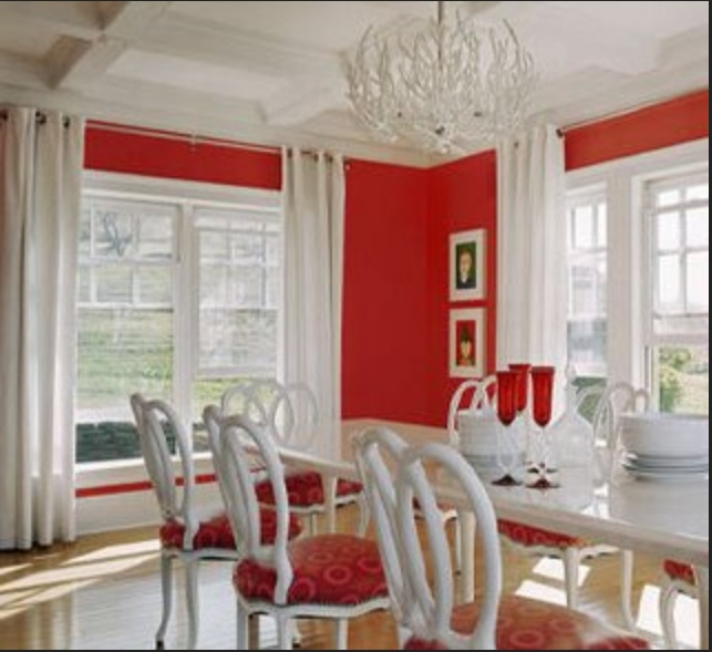 Hot red dining rooms: Red and White with a long rectangular table and two  large windows full of natural light