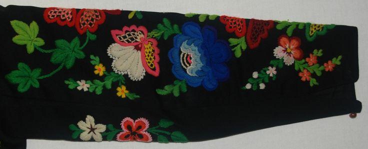 Tröja från Floda, Dalarna. På svart kläde broderi i ullgarn i livligaste färger: blommotiv i en viss stilisering. Fodrad med svart satin. Äldre katalogisering av Elisabeth Thorman (enl. uppgift).