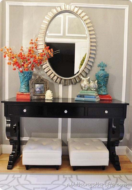 Entry way table: orchid, pic frame, white diamond accent piece, books w/ Buddha head, Apocathery jar w/ seasonal decor (pine ones, etc). Mirror behind