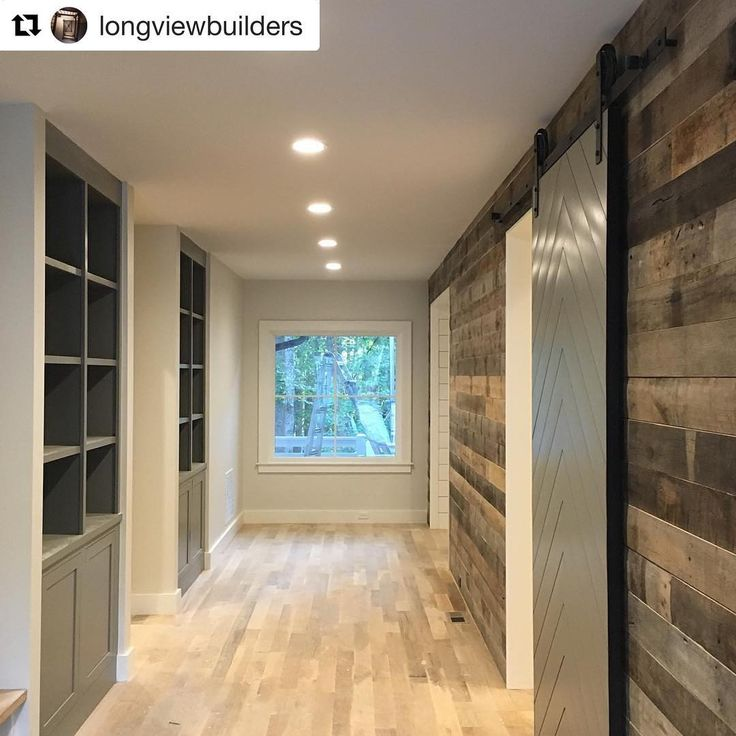 Long hallway reclaimed oak barnwood wall, custom chevron sliding barn door and custom built cabinets with grey paint (Chelsea gray by BM on door and book cases. The walls are BM Classic Gray)