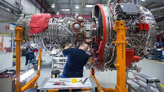 An employee works on a Rolls-Royce V2500 engine, which powers the Airbus 320 family of passenger aircraft, on the final assembly line inside Rolls-Royce Holdings Plc's aerospace unit factory in Dahlewitz, Germany.