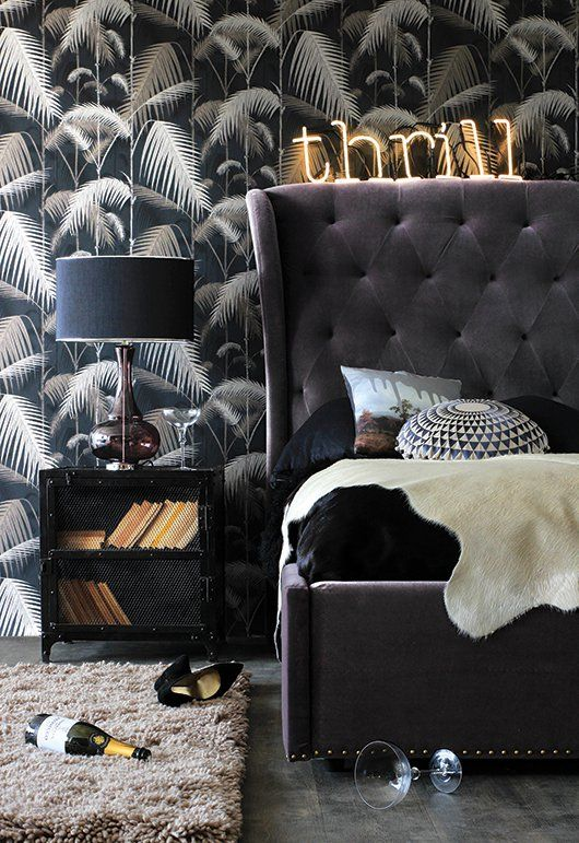 Grey velvet headboard and bed with stylish decor and patterned wallpaper
