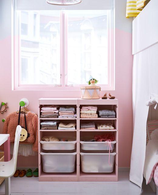 Eine Wand unter einem Fenster, davor ein TROFAST Regalrahmen in Weiß, der rosa angemalt und mit Kleidern gefüllt ist.