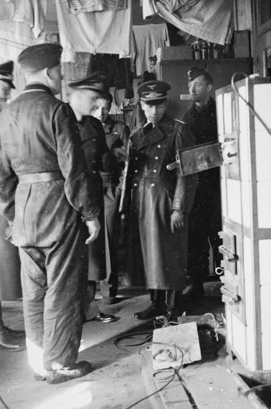 German officers looking at the entrance to a tunnel dug in a hut by POWs at Stalag Luft III located in Zagan, Poland during the Great Escape. .