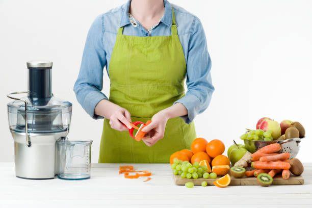 woman making fresh fruit juice using modern electric juicer