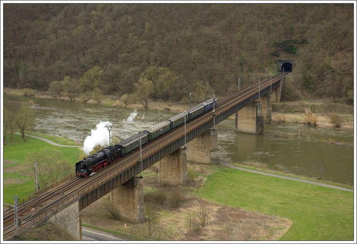 01 118 mit ihrem DRG-Schnellzug von Saarbrücken nach Koblenz war am 3.4.2010 ziemlich pünktlich unterwegs. Am Foto hat sie gerade den 367 Meter langen Petersberg-Tunnel verlassen und quert über eine 281 Meter lange Brücke die Mosel bevor sie ein paar Meter weiter die Station Ediger-Eller durchfährt. Kurz nach der Station Ediger-Eller beginnt dann der 4.205 Meter lange Kaiser-Wilhelm-Tunnel. Das Tageslicht wird sie dann erst wieder kurz vor dem Bahnhof Cochem erblicken.   (70 mm Version)