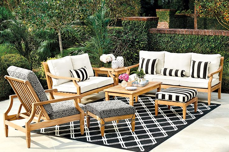 Black and white canopy stripe pillows on outdoor teak furniture