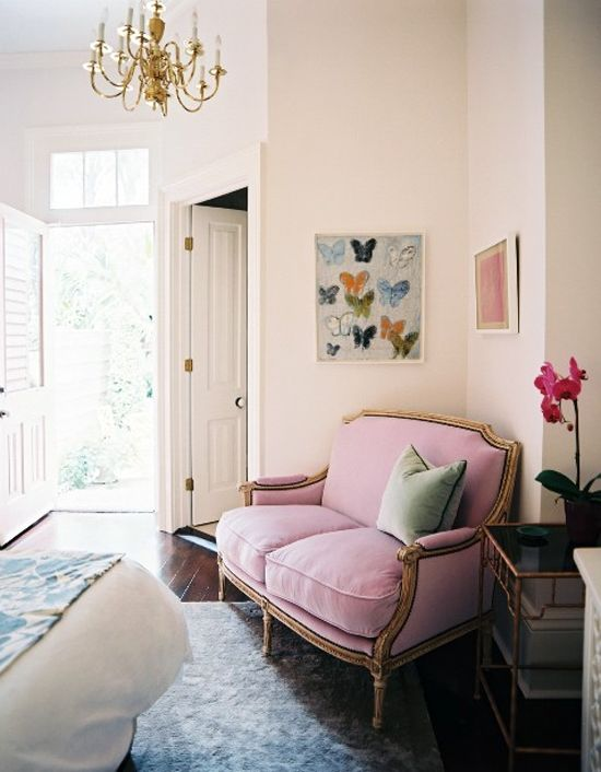 antique brass bamboo side table, chandelier, butterfly art, and pink velvet settee.
