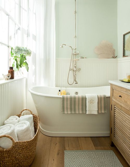 Small but gorgeous spa-like bathroom with blue green walls paint color, freestanding tub, chair rail with beadboard, blue diamonds bath mat, seafan art and oak single bathroom vanity with marble countertop.