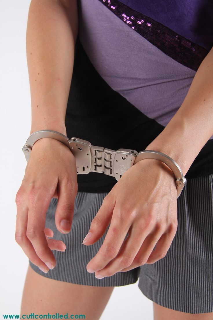 Woman's hands in hinged handcuffs.