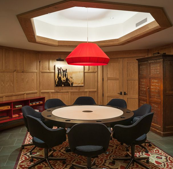 This stylish poker room in New York, designed by Sandvold Blanda Architecture + Interiors, includes a statement-making oversized red pendant light, a custom designed poker table and modern office chairs.