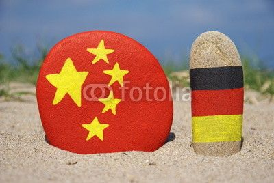 China and Germany's flags on stones with sand background