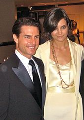 Holmes and Tom Cruise together, her hand on his shoulder.