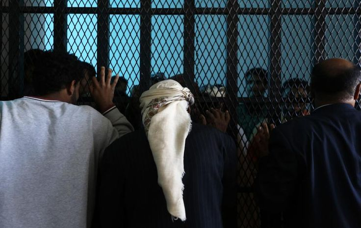 Relatives talk with defendants from behind bars in a state security court of appeals in Sanaa, Yemen, February 10, 2015. The court upheld jail verdicts ranging from three to seven years on 13 people condemned of supporting the al Qaeda group in Yemen, court officials said. REUTERS/Khaled Abdullah
