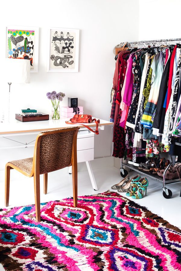 A cheetah-patterned chair and colorful Moroccan rag rug are tempered by the simplicity of a white table and lucite lamp. Closet space is limited, so a rack holds the overflow in this corner space.