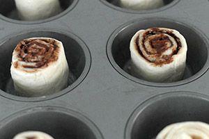 Verwarm de oven op 200 graden. Haal het croissantdeeg uit het blik volgens de verpakking. Vouw de rol met deeg af tot een lange lap en snijd in drieeen bij de verticale perforatielijnen. De schuine naden laat je aan elkaar. Besmeer de stukken deeg met een laagje chocolade pasta en verdeel wat nootjes er over. Rol de lap deeg op en snijd in 3 stukken. Vet een muffinbakblik in met een beetje boter. Leg de rolletjes deeg hier in zet ze ongeveer 12 minuten in de oven.