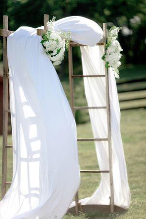Jolie arche composée d'une double échelle, d'un voilage et de fleurs