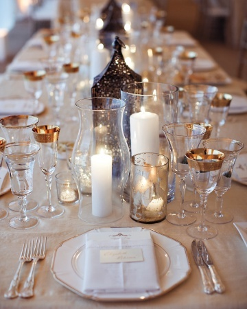 Neutral linens and bronze lanterns, hurricane lamps, and candles