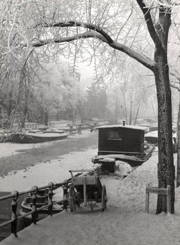 Besneeuwde gracht in Amsterdam. Boten, bomen, een handkar, daken: alles is wit. Amsterdam, 29 december 1939.