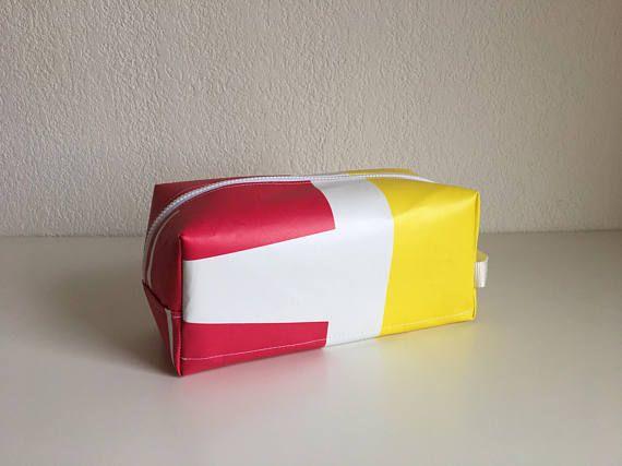 Trousse de toilette en bâche publicitaire recyclé, de fabrication artisanale. Trousse de toilette en bâche publicitaire recyclé de couleur blanche, rose et jaune. Il y a une poche intérieur et une sangle sur le côté. Elle se ferme à laide dune fermeture. Lavable à la main, un coup