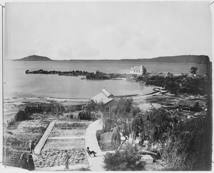 Gardens of the Lake House Hotel. View across Ohinemutu shouing St Faith's Church and Lake Rotorua, New Zealand. Photo by Elizabeth Pulman, early 1880s from Alexander Turnbull Collections