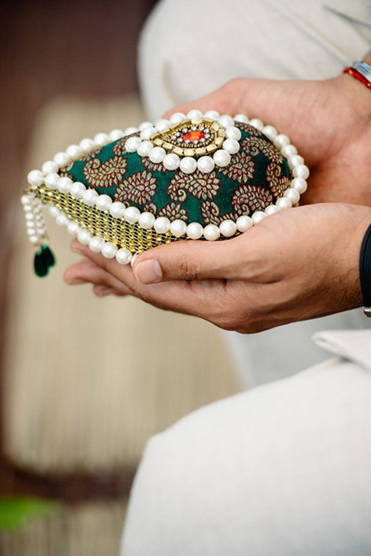 Pavit holding an embroidered coconut. The bride's family walks to the entrance carrying a coconut to receive the groom's party. The coconuts are then exchanged as a symbol of the marriage contract.