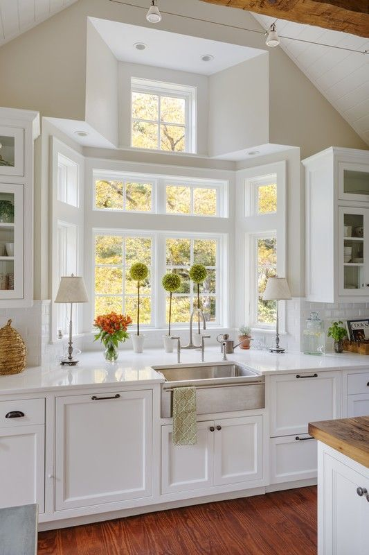 This vibrant kitchen contains a large sink in front of windows for a relaxing view.