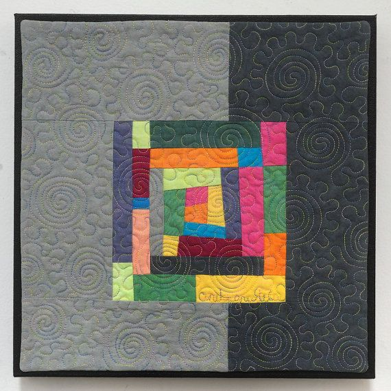 """""""First Crocus"""" - 12"""" x 12"""" quilted wall hanging with an improvisational log cabin center and gray borders. Quilted with a whimsical spiral and jigsaw puzzle design. Mounted on painted black canvas."""