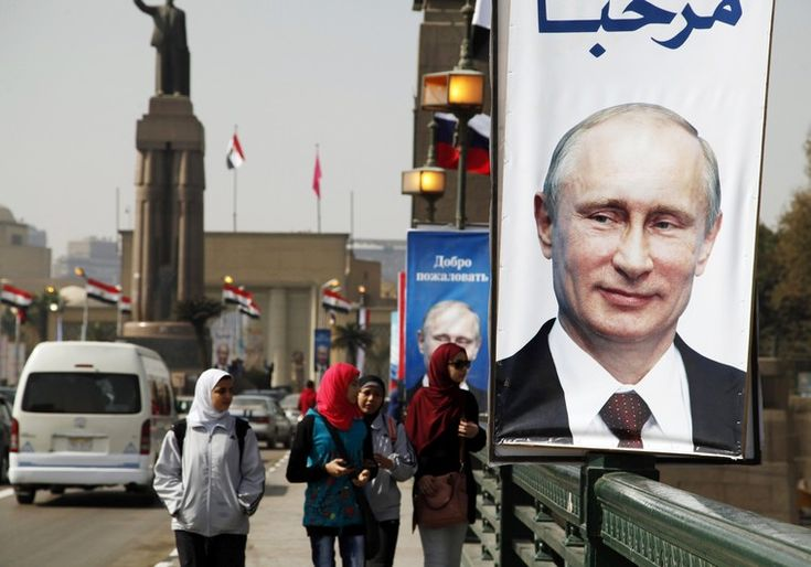 PUTIN TO ARAB LEAGUE: PALESTINIANS HAVE A RIGHT TO STATE WITH CAPITAL IN EAST JERUSALEM - Girls walk past a banner with a picture of Russian President Vladimir Putin along a bridge, in central Cairo Photo By: REUTERS