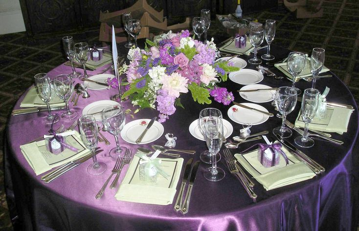 Image from http://www.homipix.com/wp-content/uploads/2015/02/interior-round-table-with-purple-tablecloth-combined-by-white-purple-flower-bouquet-with-gift-on-over-white-napkin-and-cutlery-set-beautiful-looks-of-wedding-party-table-decoration-ideas-with-pretty-d.jpg.