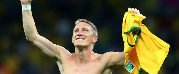 Bastian Schweinsteiger holds a Brazil shirt aloft