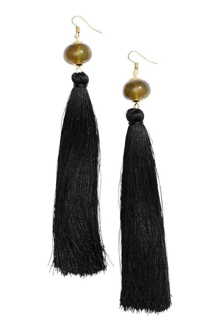 Oorbellen met kwastje: Een paar metalen oorbellen met een kunststof kraal en een lang kwastje van textiel. Lengte 16 cm.