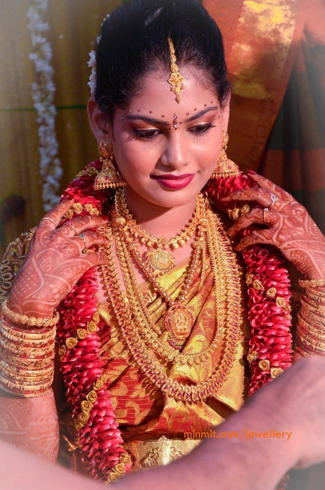 Traditional South Indian bride wearing bridal saree, jewellery and hairstyle. Indian wedding photography.