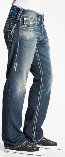 Bold, signature Super-T stitching defines amply distressed and holed denim  jeans