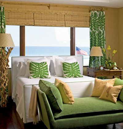 Natural materials such as matchstick blinds, bamboo drapery hardware, and a driftwood lamp lend rustic accents to this tropical bedroom.