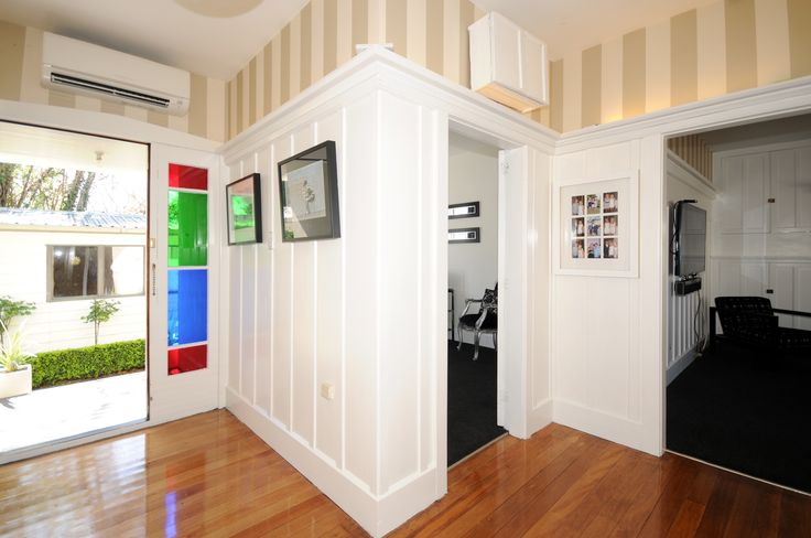 Entrance way, wooden paneling painted white, heritage stripe wallpaper, wooden floors