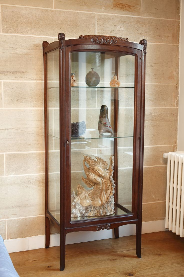 An early 20th century natural sculpted wood showcase decorated with stylized flowers and foliage in Art nouveau taste, resting on four curved feet. The delicacy of sculptured ornaments and t