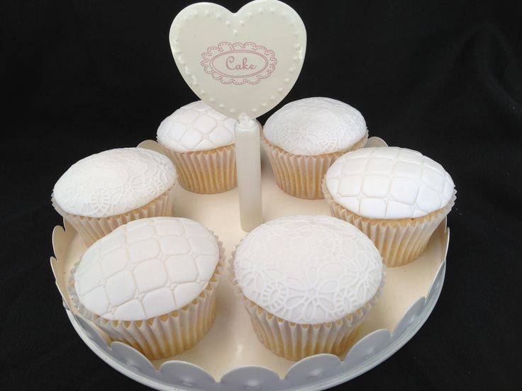 Wedding cupcakes.  White chocolate mud cupcakes covered in embossed fondant.