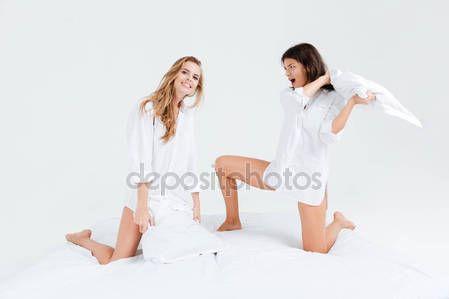 Скачать - Две счастливые веселых женщин, которые борются с подушками в постели — стоковое изображение #129966824